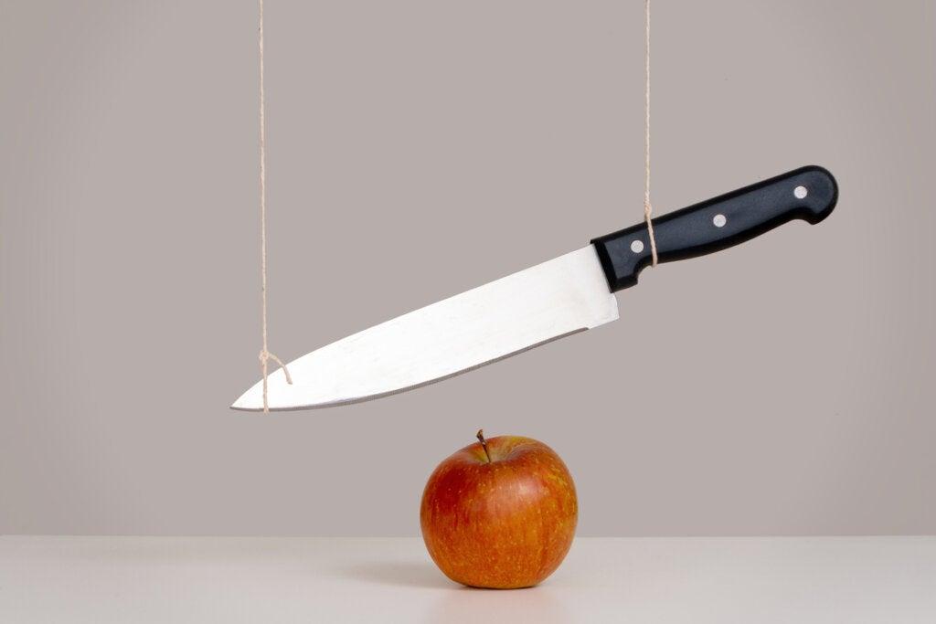 Cuchillo sobre manzana para representar el concepto de la espada de Damocles