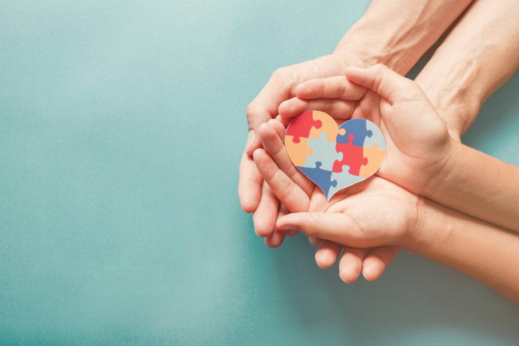 Manos de una madre y una hija con un corazón con los colores del autismo