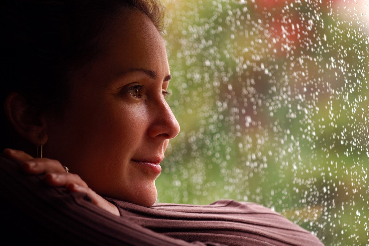 Mujer sonriendo mirando por la ventana