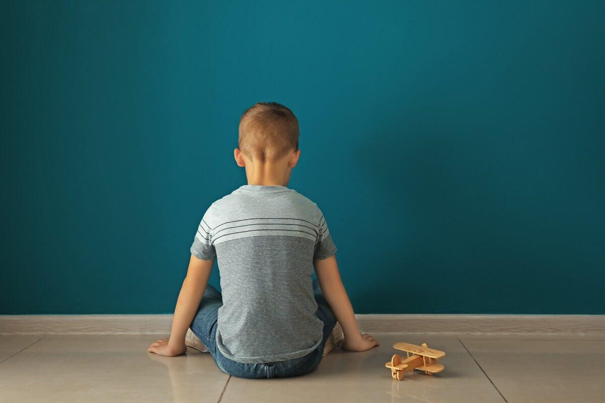 Niño con autismo sentado frente a la pared
