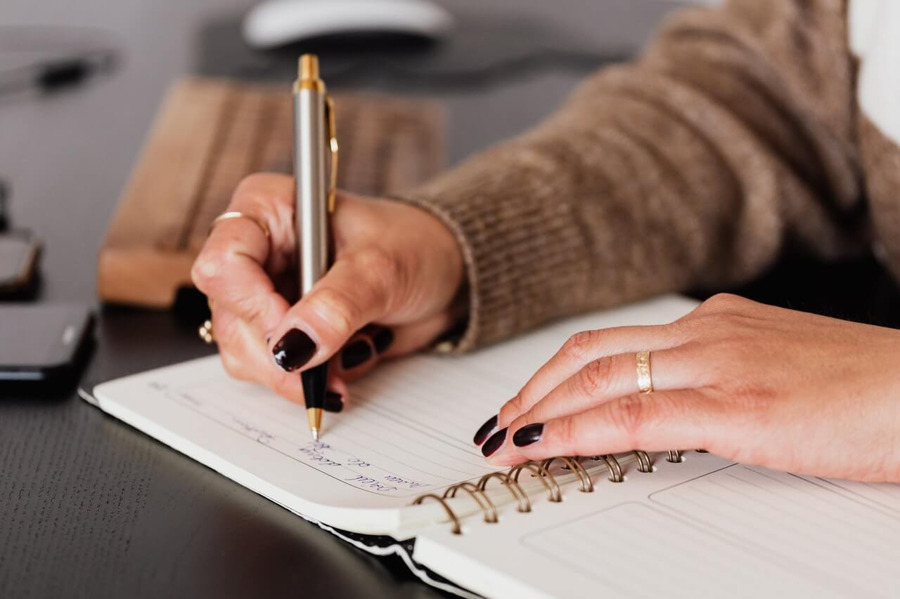 Mujer anotando en una libreta su plan de crecimiento personal.
