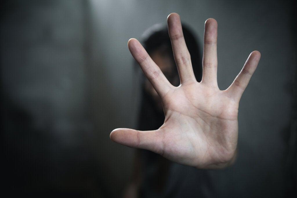 Mujer haciendo señal de alto con la mano.