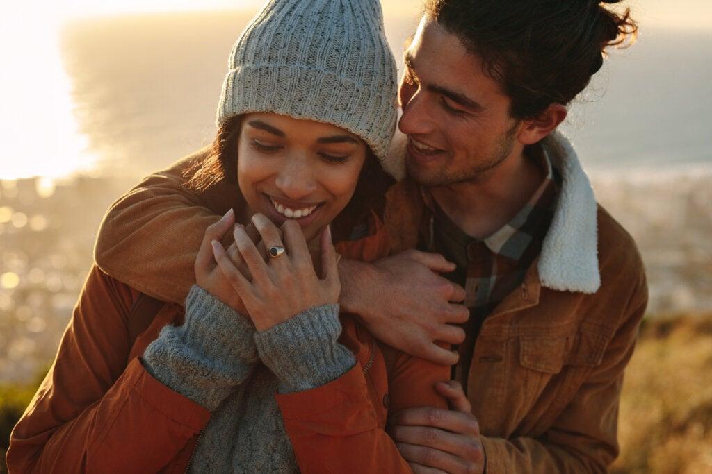 Chico abrazando a su novia en invierno