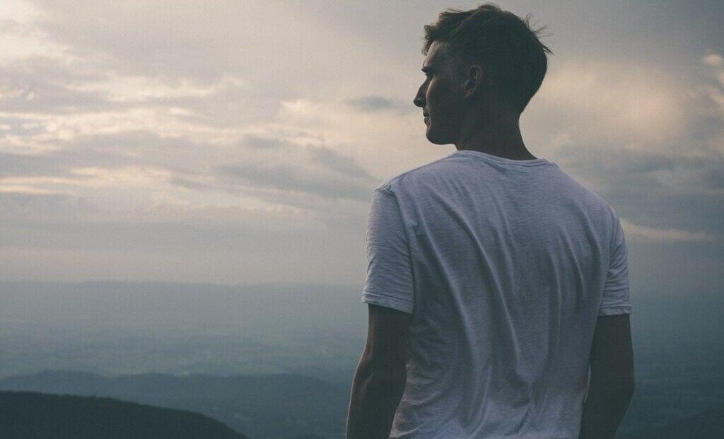 Hombre mirando al mar pensando en frases motivadoras y de superación personal