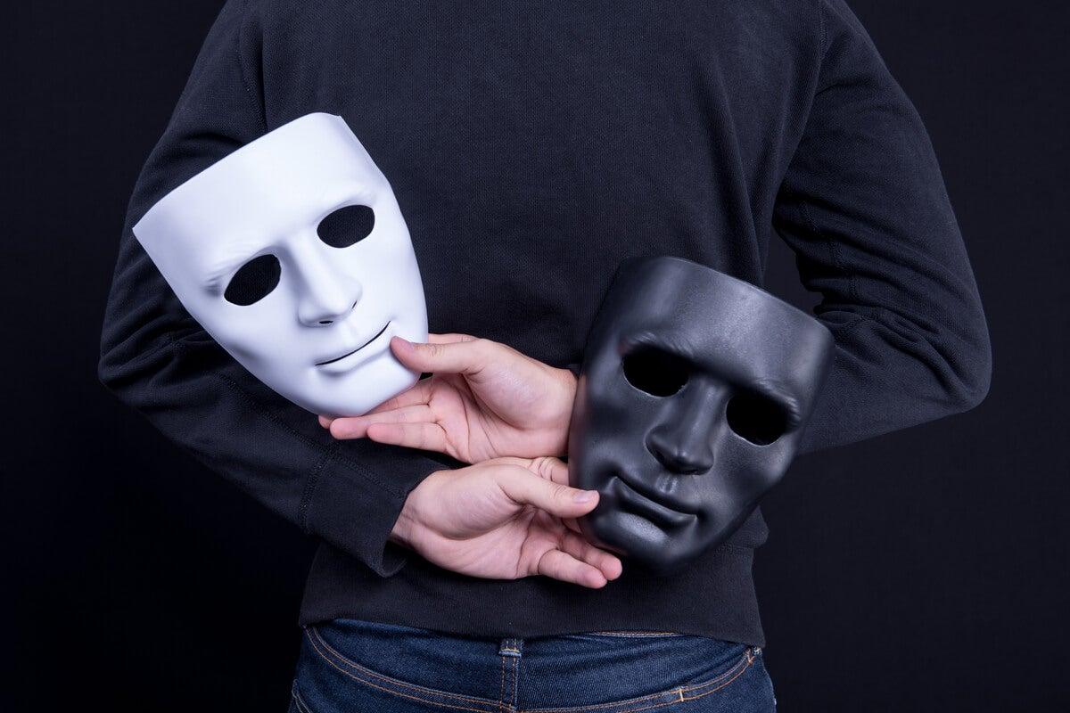 Hombre ocultando dos máscaras como gesto de hipocresía