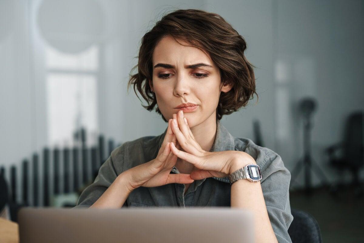 Mujer concentrada en el ordenador pensando en las preguntas sin respuesta