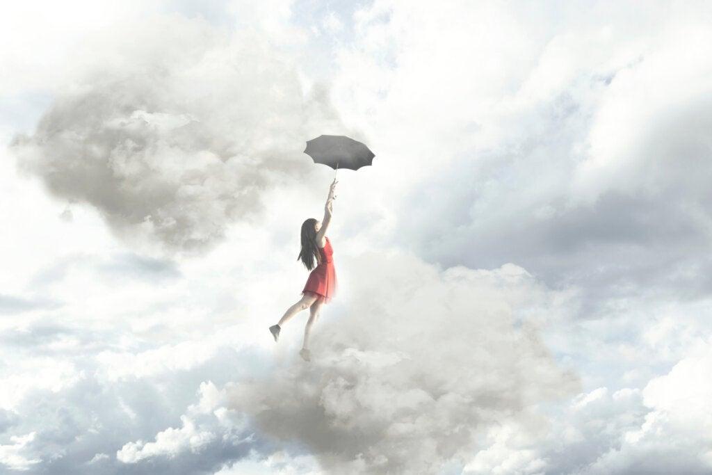 Mujer volando con un paraguas entre nubes pensando que no hay límites