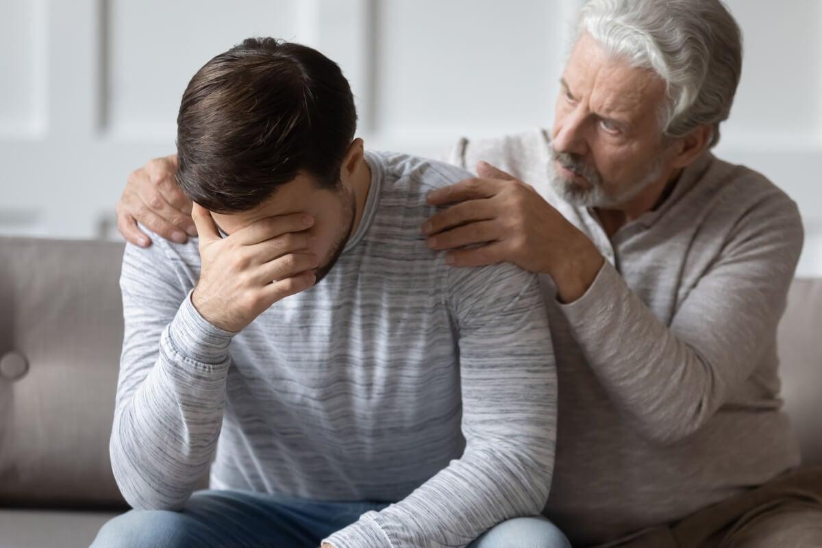 Padre consolando a su hijo con problemas de pensamiento desorganizado y comunicación