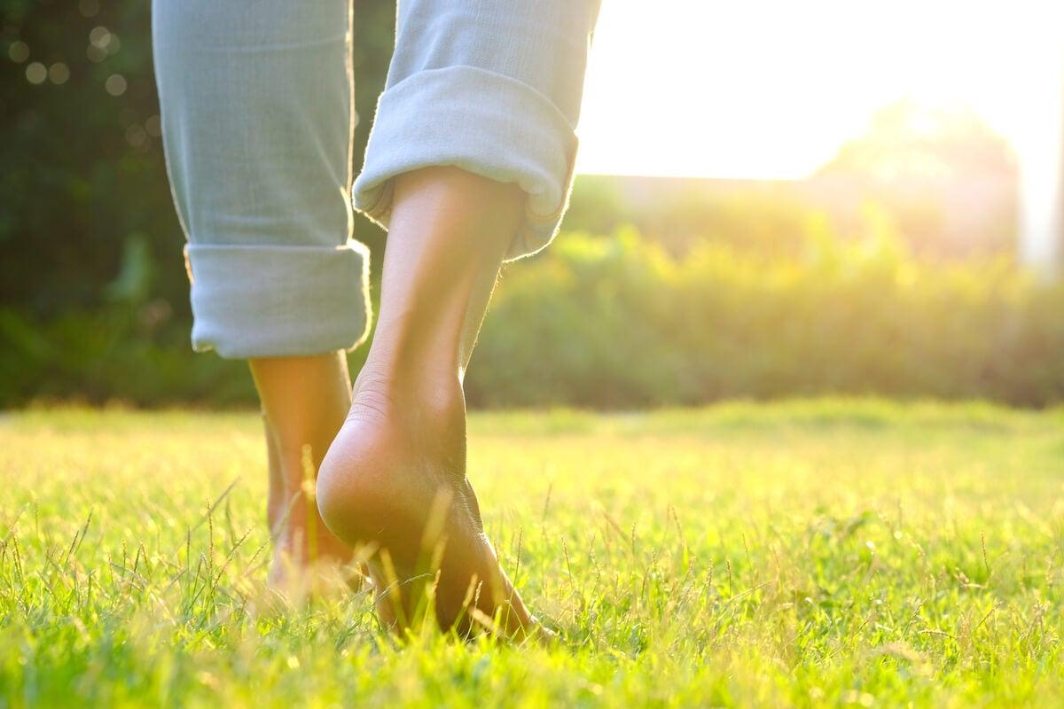 Persona andando descalza por césped