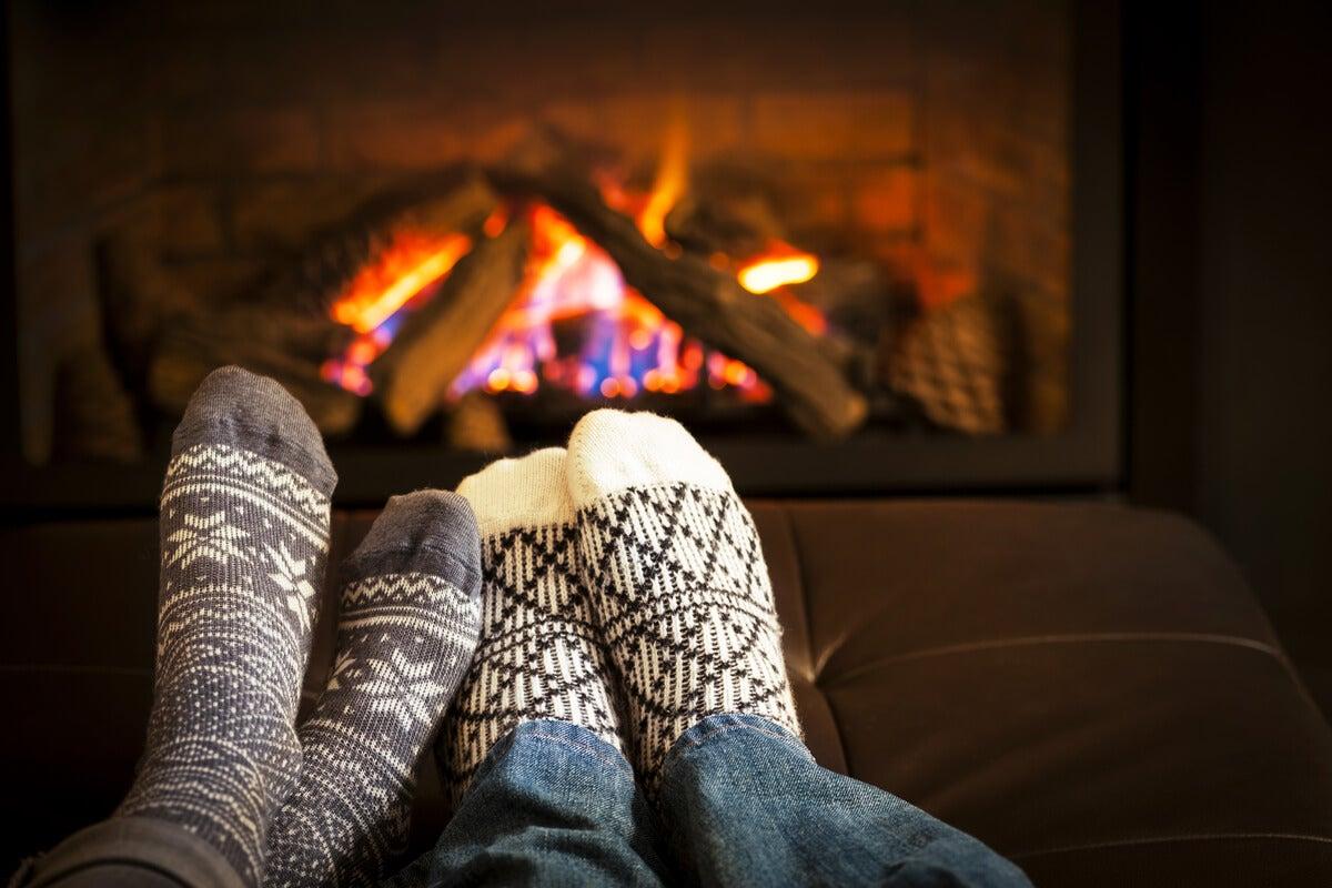 Pies con calcetines de una pareja frente a la chimenea practicando el cuffin season