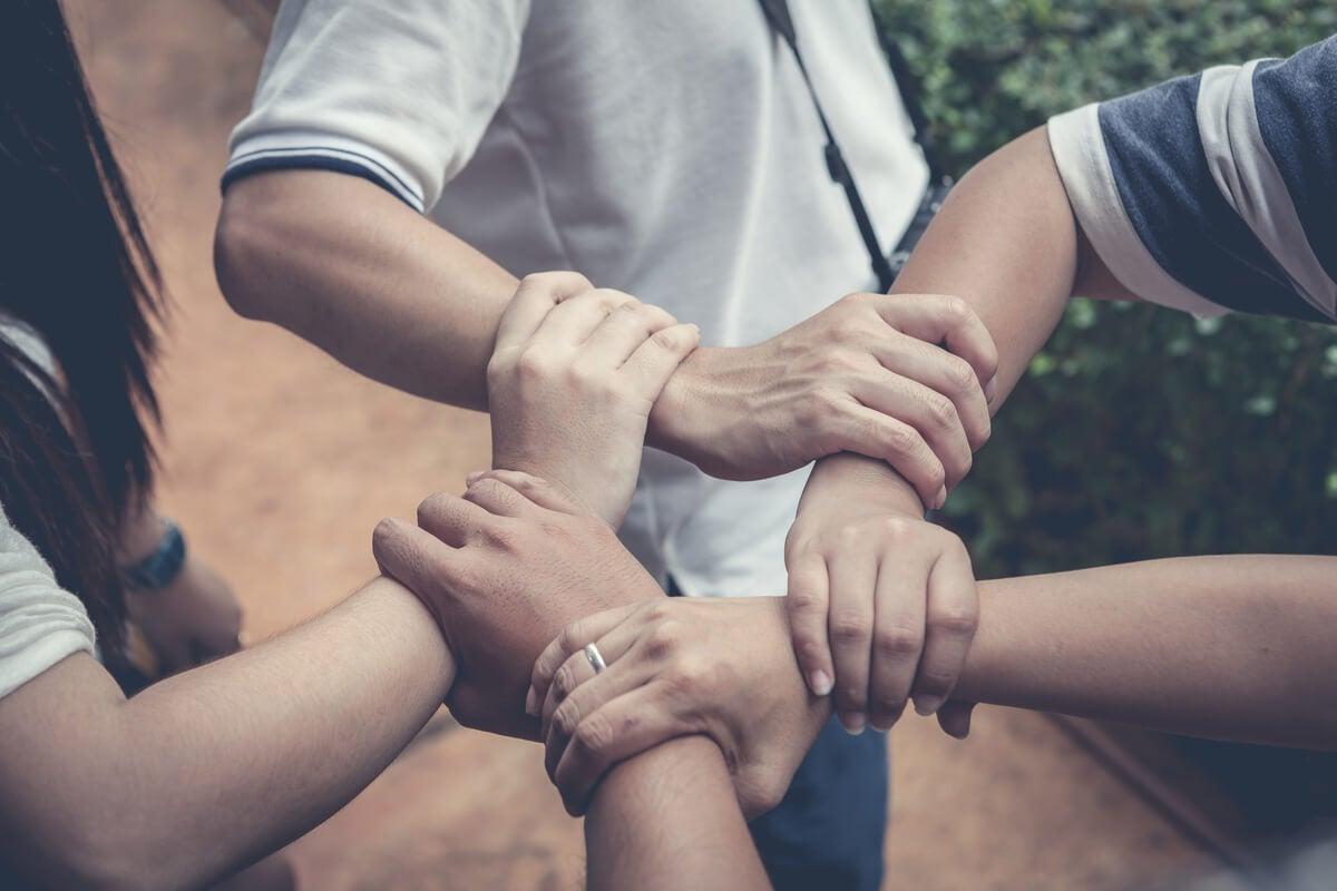Grupo de personas agarrando sus brazos para ayudarse