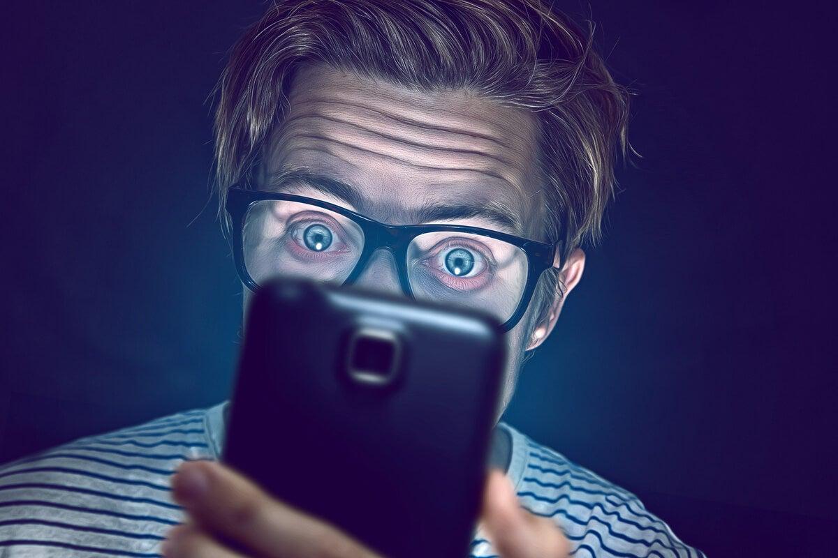 Hombre viendo móvil simbolizando la ciberpsicología