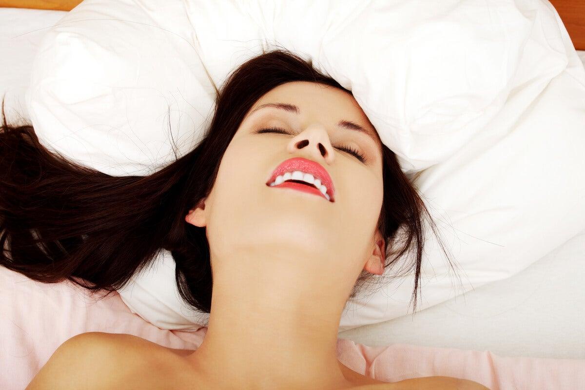 Mujer en la cama sonriendo por orgasmo