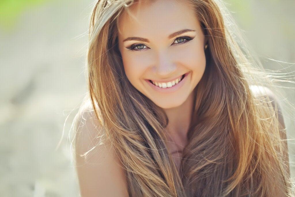 Vakker kvinne som smiler og bruker hemmeligheten for å gjøre et bedre inntrykk