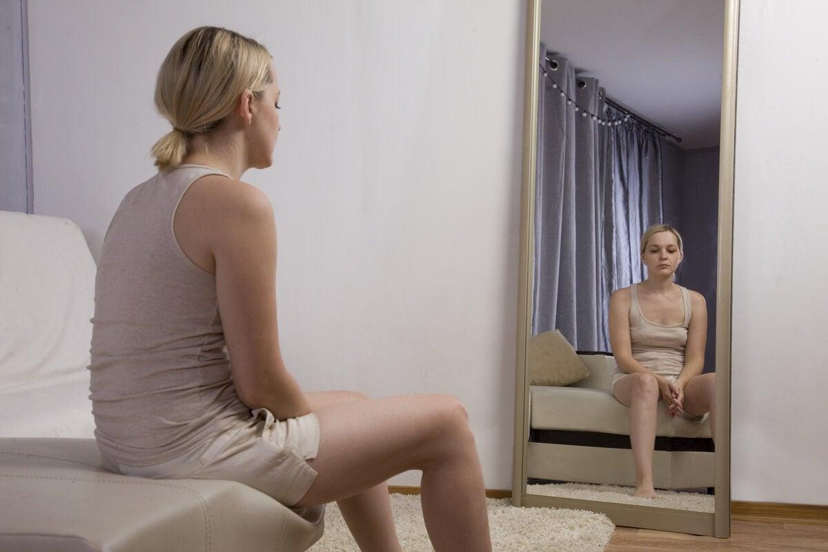 Mujer mirándose al espejo triste