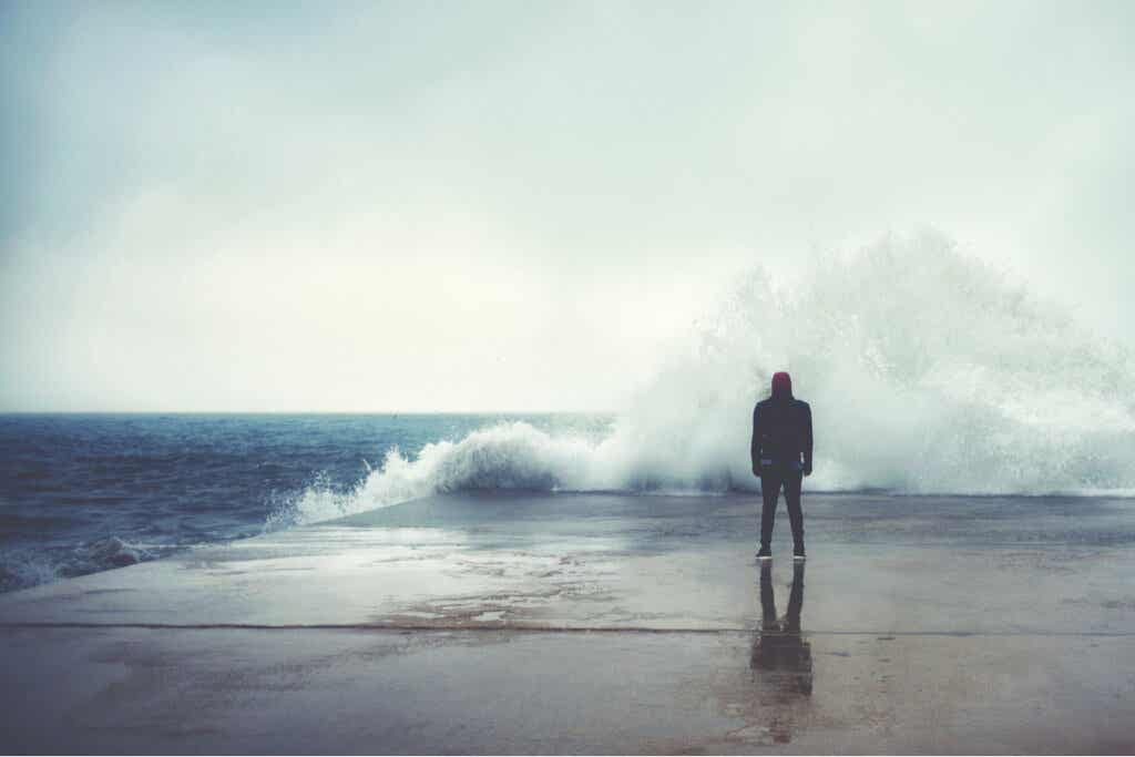Hombre frente a una ola del mar que sufre psicastenia