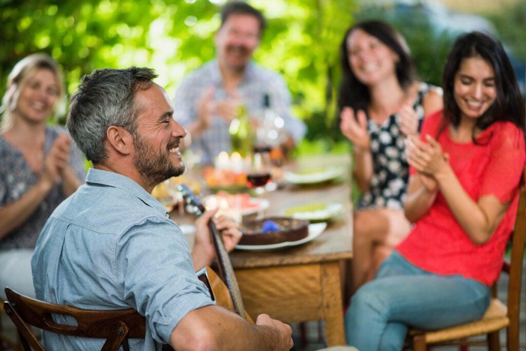Hombre tocando una guitarra en una comida de amigos disfrutando del Sentimiento de pertenencia