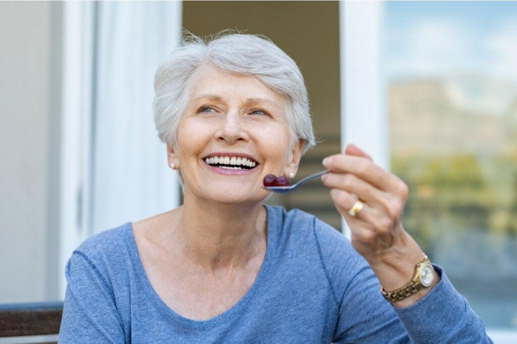 Mujer mayor comiendo uvas rojas