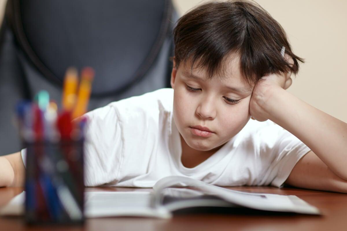 Niño estudiando agobiado