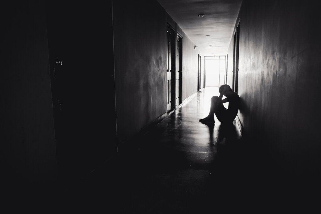 Niño sentado en el suelo en la oscuridad