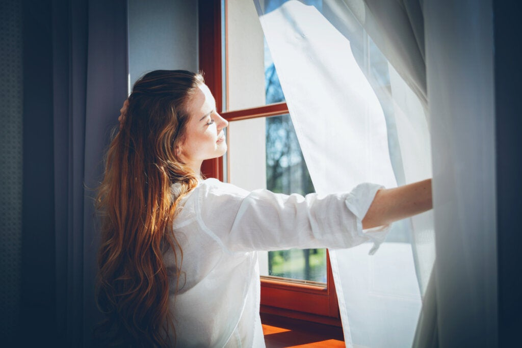Mujer abriendo una ventana