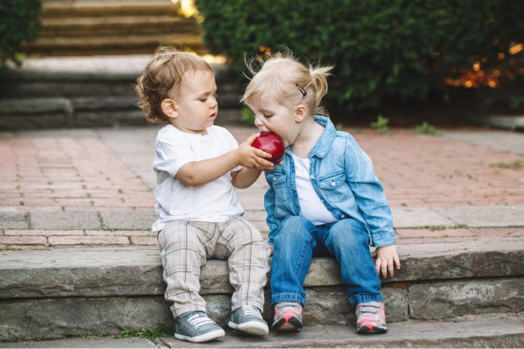 Niño pequeño dando una manzana a otra niña
