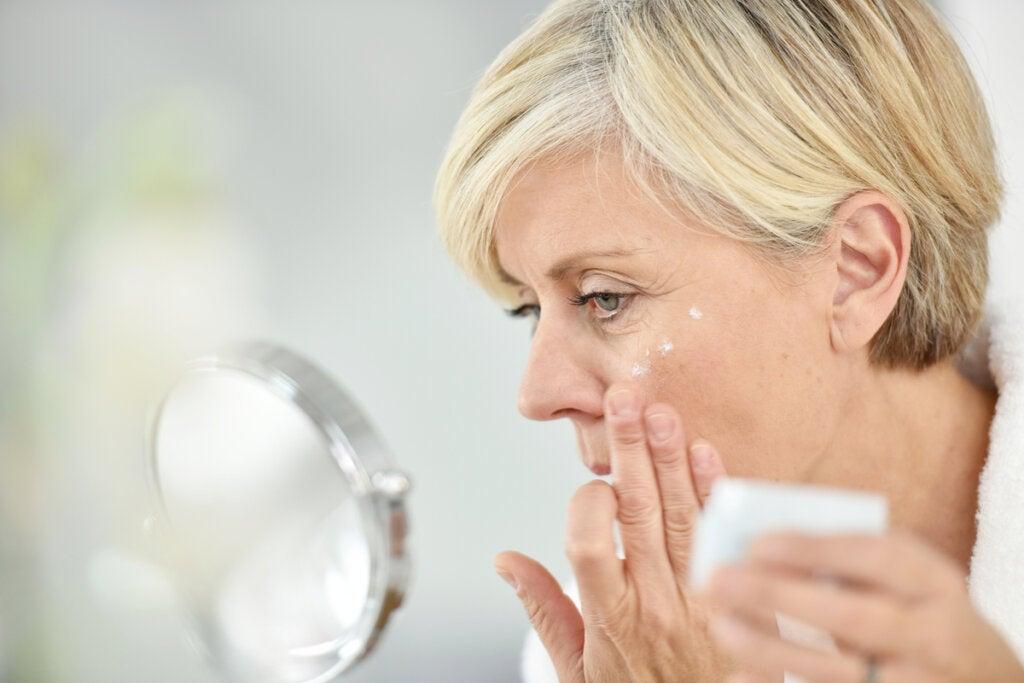 Mujer de mediana edad echándose crema en la cara