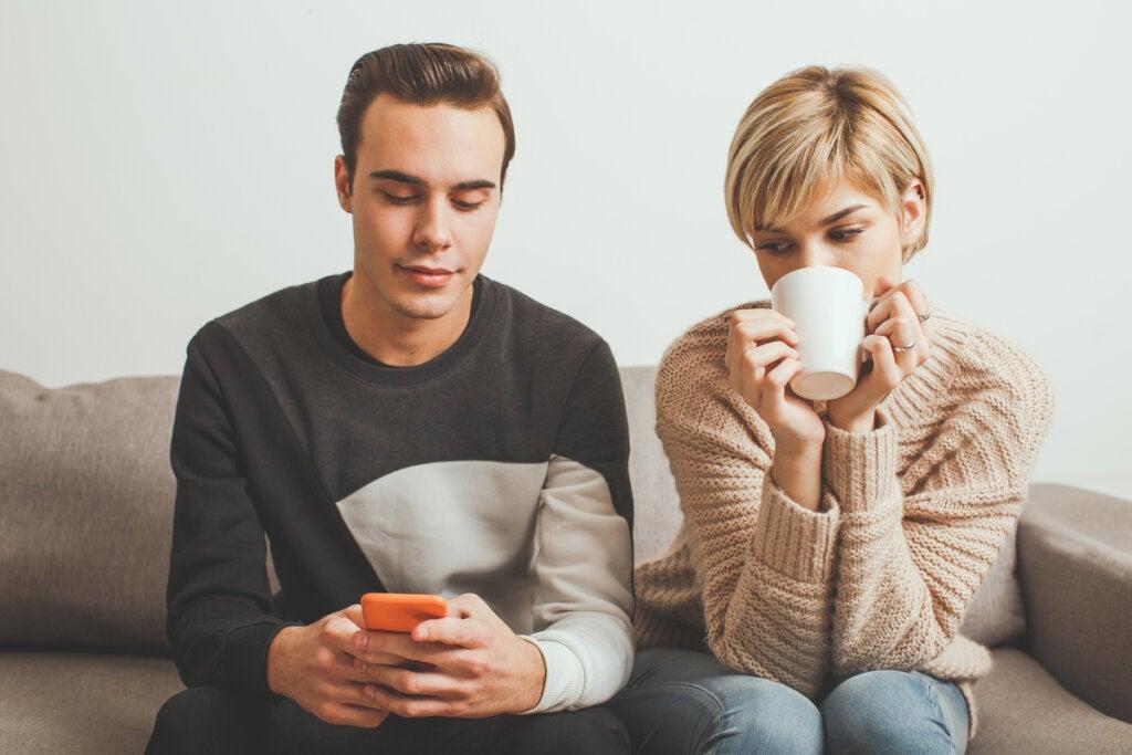 Mujer mirando las conversaciones del móvil de su novio