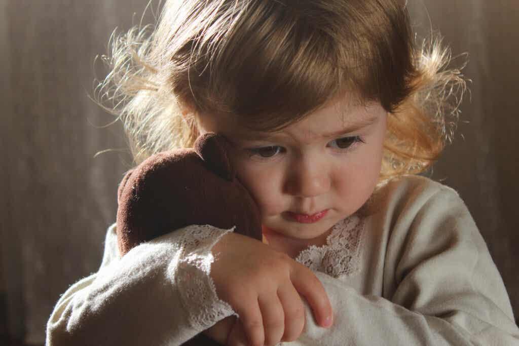 Niña triste abrazada a un peluche