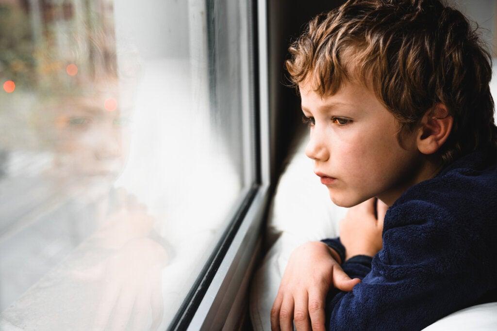 Niño triste mirando por la ventana que sufre aislamiento afectivo