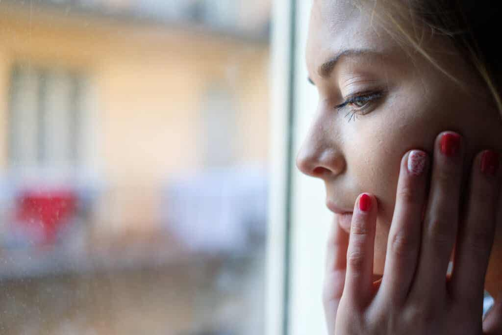 Mujer preocupada mirando por la ventana