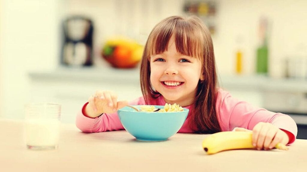 niña con bol cereales simbolizando la importancia del desayuno en el rendimiento escolar