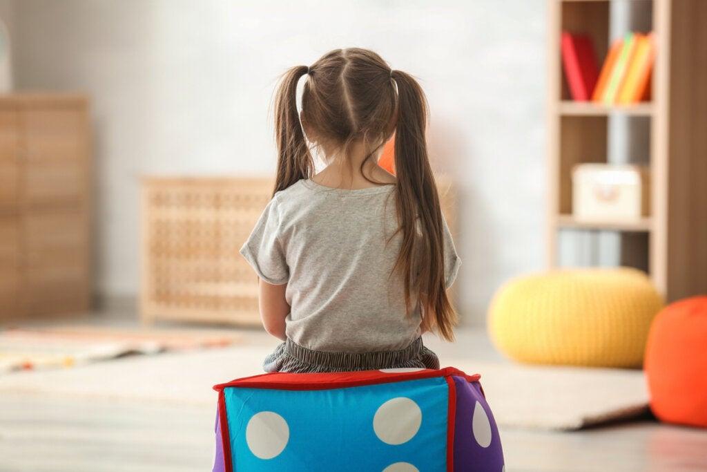 Niña de espaldas sentada en un sillón en forma de dado