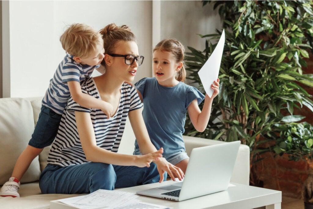 Madre trabajando estresada por sus hijas