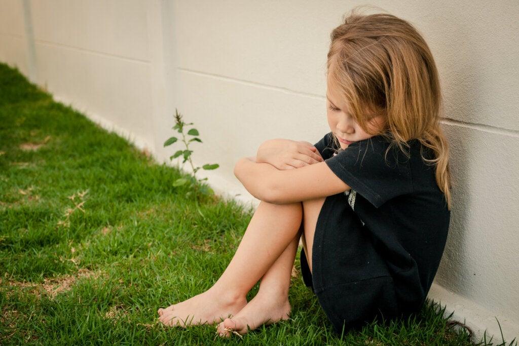 Niña triste sentada en el suelo