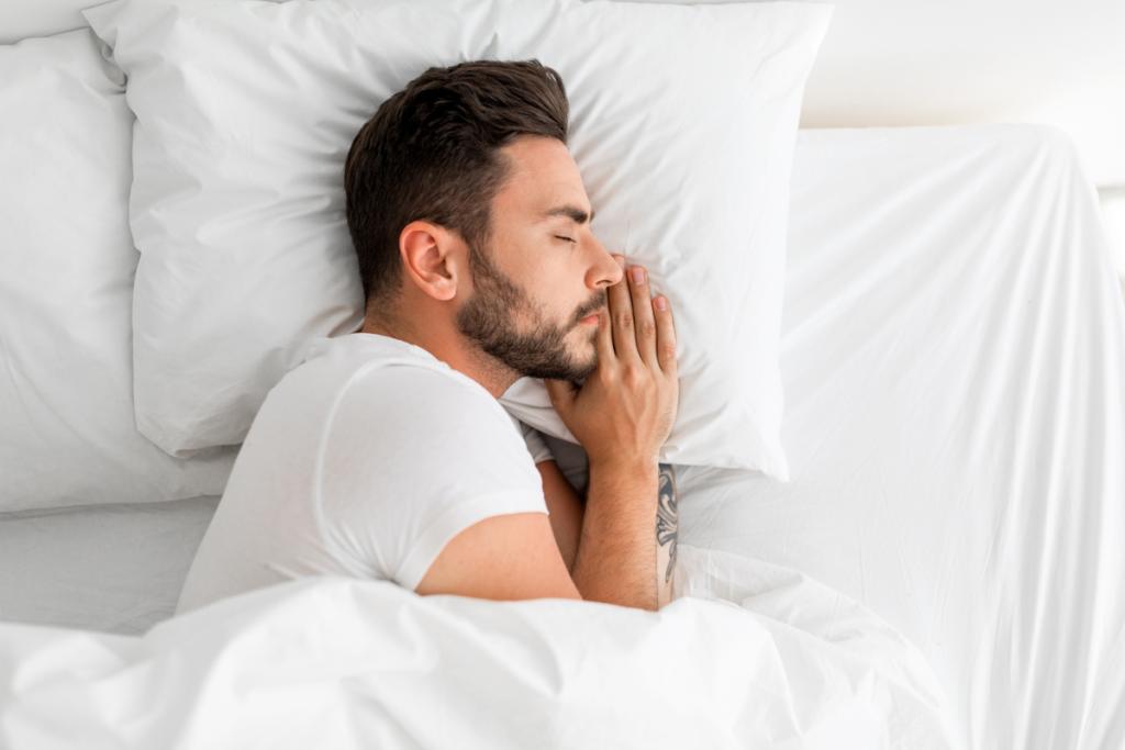 Sovende mann med hånden under pute