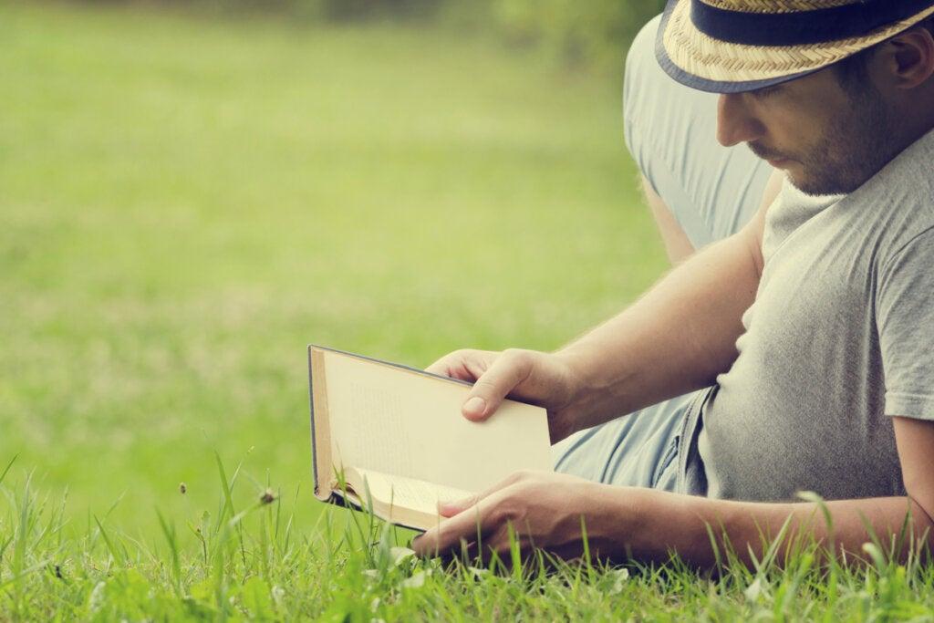 Çimenlerin üzerinde kitap okuyan adam