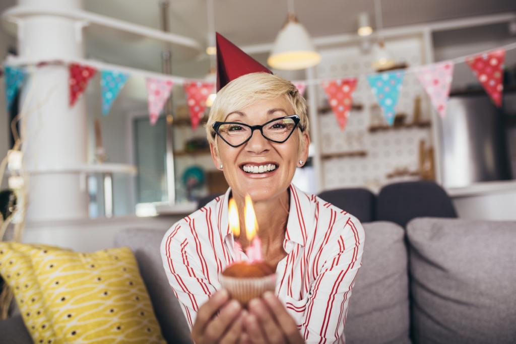 Senior kvinne som feirer bursdag og får bursdagshilsener