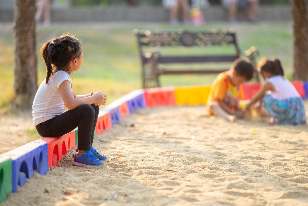Pikkutyttö katselee muiden lasten leikkiä.