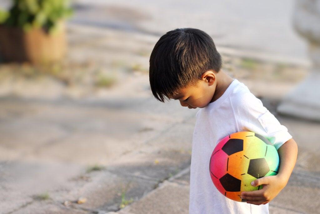 Niño con un balón sin amigos