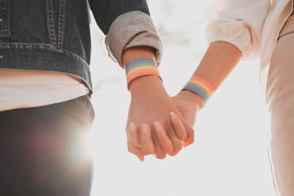 A gay couple walking hand in hand.