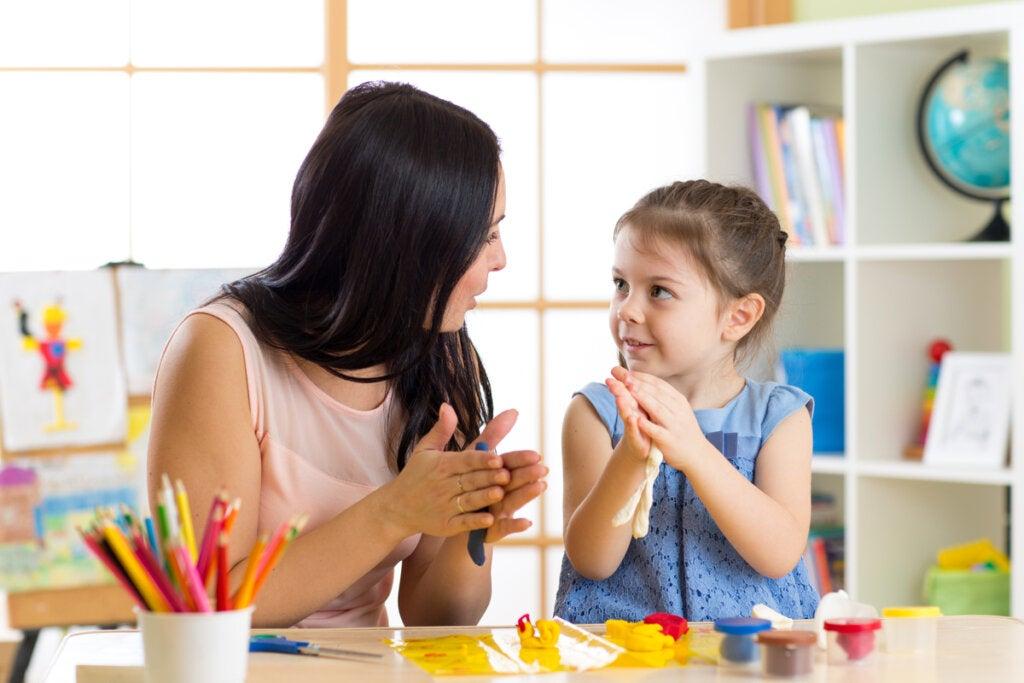 Matka rozmawia z córką podczas tworzenia kształtów za pomocą plasteliny